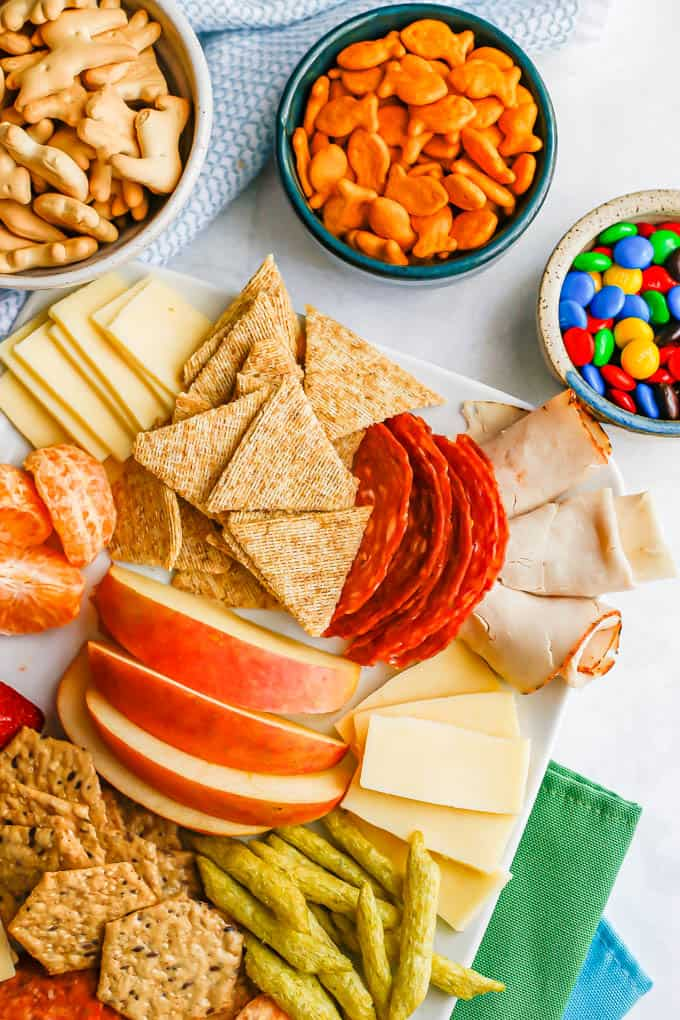 Close of of one side of a cheese board for kids with bowls of animal crackers, Goldfish and M&Ms nearby