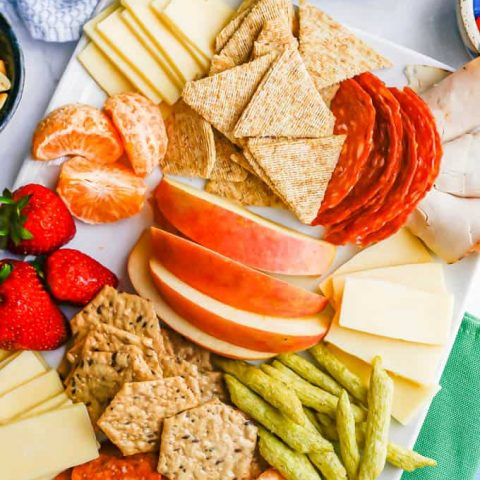 A white platter filled with cheese, crackers, cured meats, fruits and snacks for kids