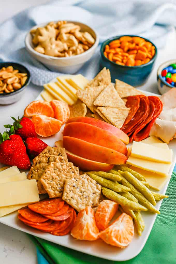 Side angle view of a big snack board with extra bowls in the back for more snacks