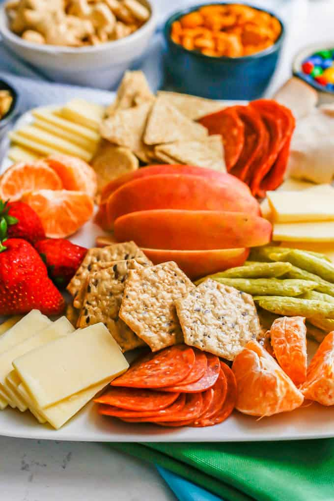 Close up of cheese, crackers, pepperoni slices and mandarin orange slices as part of a large kids charcuterie board