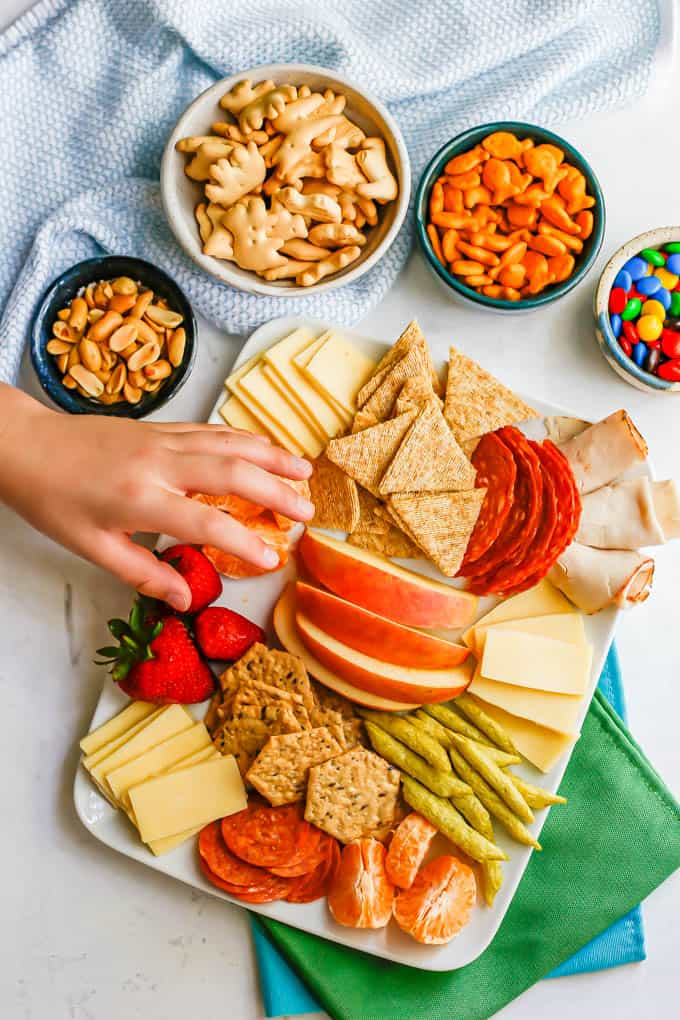 A small hand reaching toward a white platter of cheese, crackers and snacks for kids with small bowls of snacks to the back