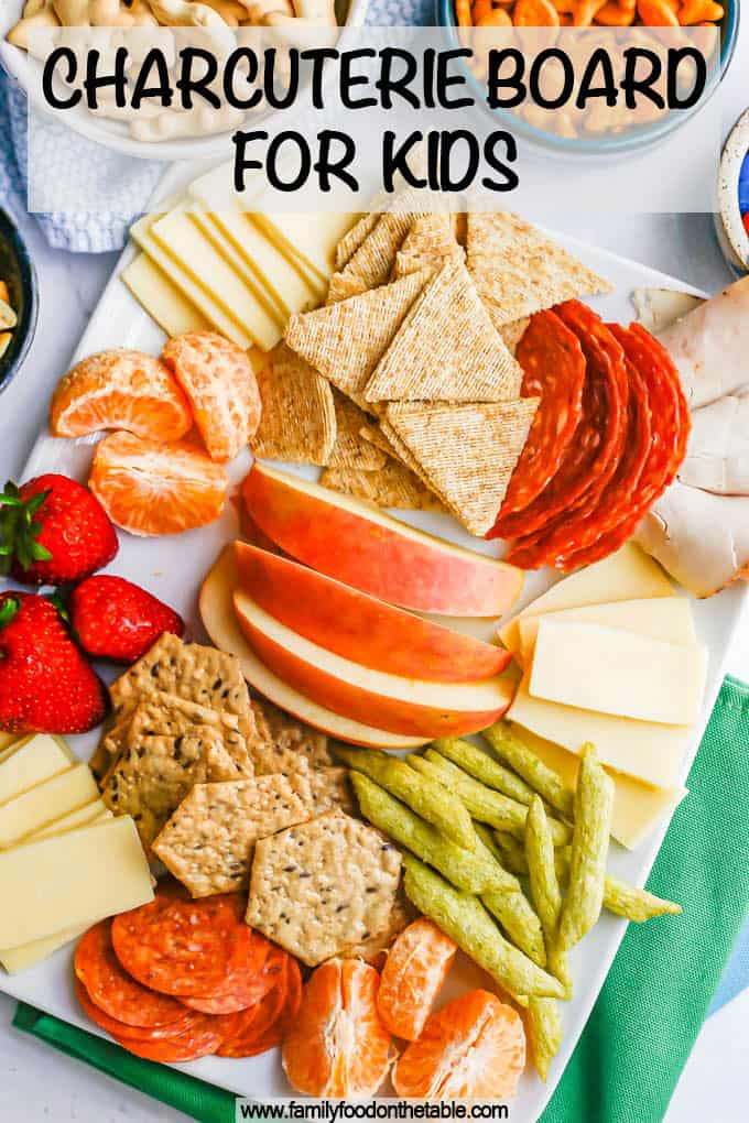 A white platter filled with cheese, crackers, cured meats, fruits and snacks for kids with a text overlay on the photo