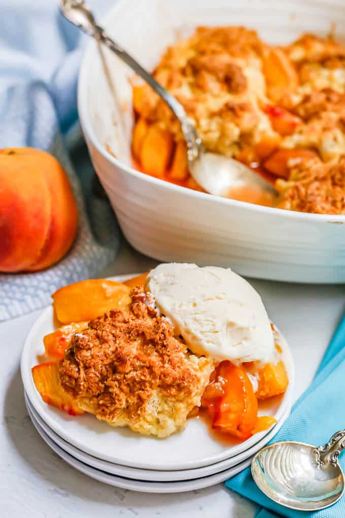 A scoop of ice cream on top of peach cobbler on a small serving plate, with the casserole dish in the background