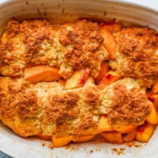 Peach cobbler in a white casserole dish after being baked