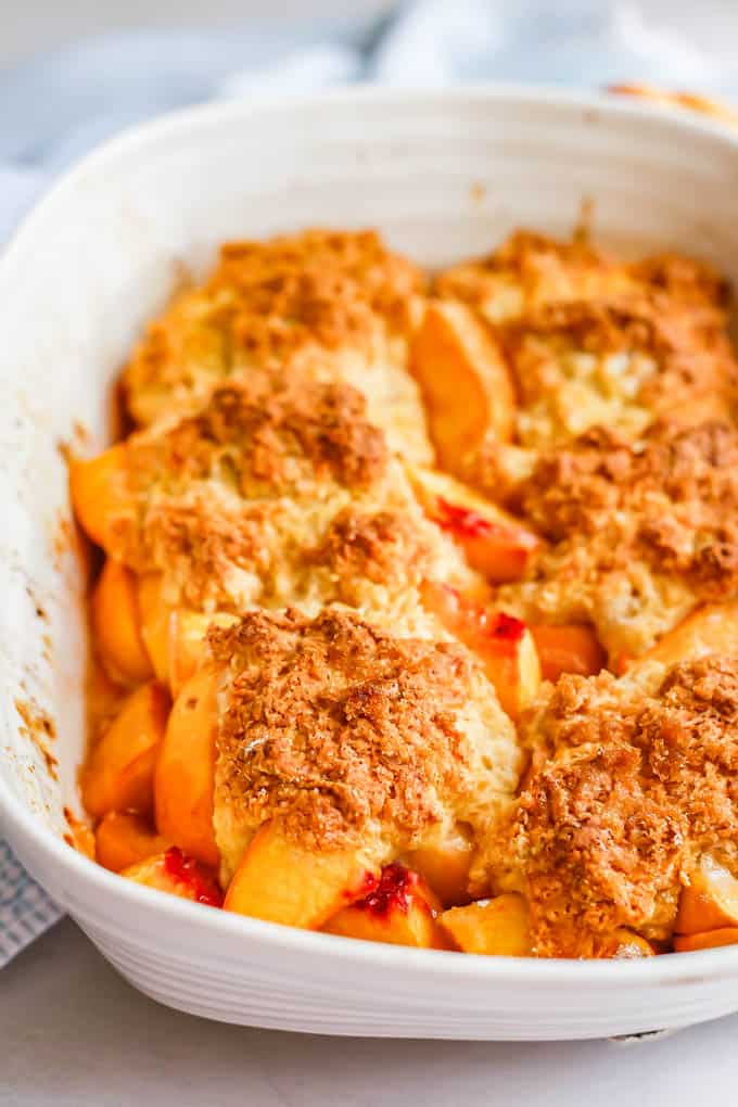 A baked peach dessert with sweet biscuits on top in a white casserole dish