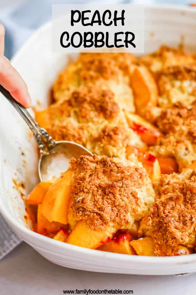 A serving spoon lifting a scoop of fresh peach cobbler out of a white casserole dish and a text overlay on the photo