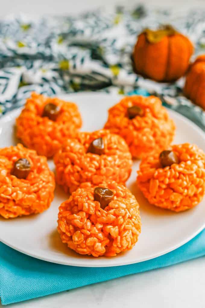 A white plate of orange pumpkin Rice Krispies with tootsie roll stems