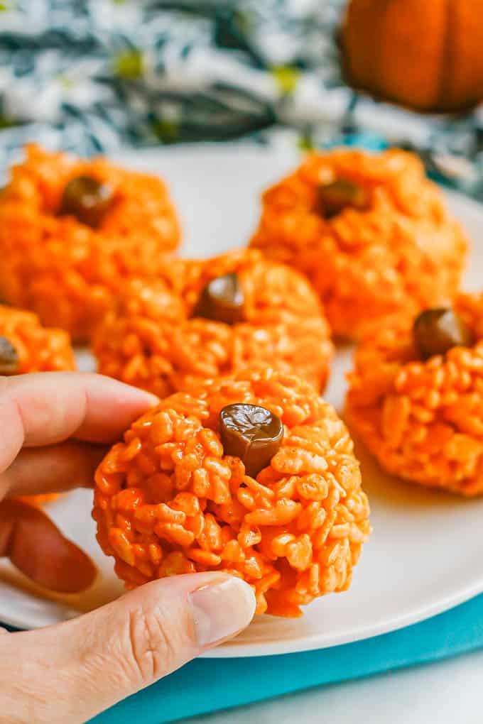 A hand holding an orange pumpkin rice Krispie treat with a tootsie roll stem