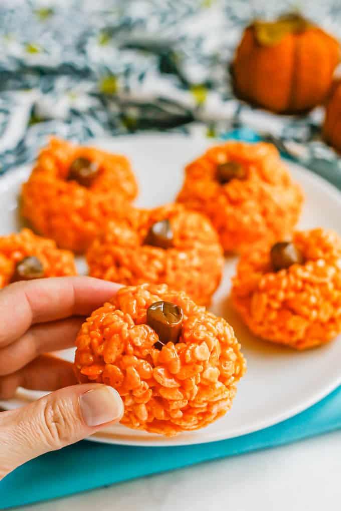 A hand picking up a pumpkin Rice Krispie treat from a plate