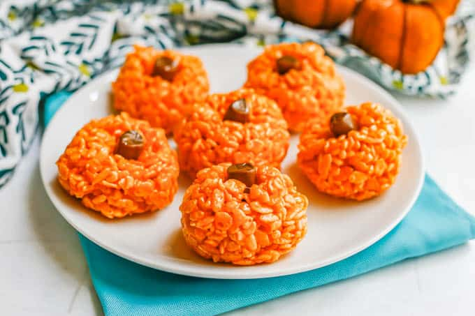 A plate full of rice Krispie treats in the shape of pumpkins with a tootsie roll for a stem