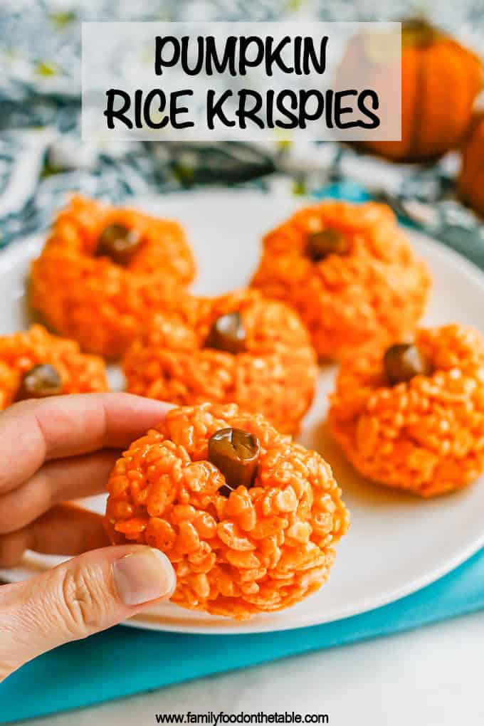 A hand picking up a pumpkin Rice Krispie treat from a plate with a text overlay on the photo