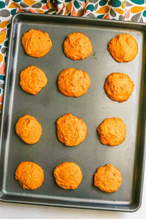 A baking sheet with a dozen pumpkin cookies after being baked in the oven
