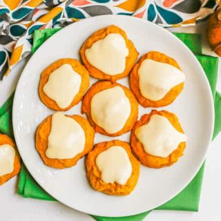 A plate full of pumpkin cookies with orange icing on top