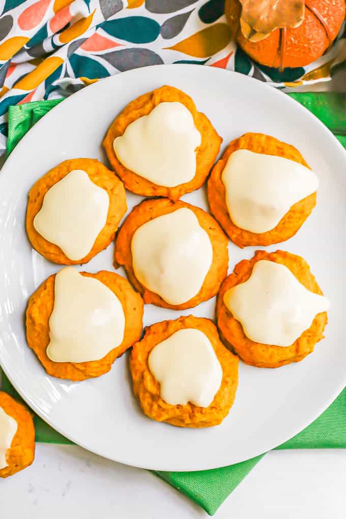 Overhead shot of a white plate with pumpkin cookies on top of green napkins with a colorful towel to the back
