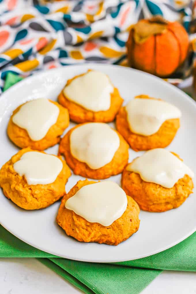 A white plate with 7 pumpkin cookies topped with a white icing, with green napkins underneath