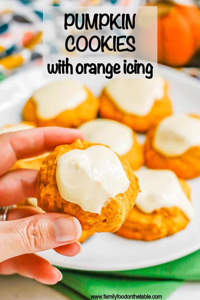 A hand holding a small pumpkin cookie with orange icing up from a white plate with a text overlay on the photo