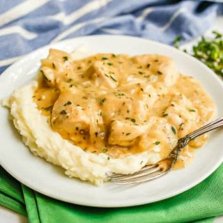 Chicken and gravy over mashed potatoes on a white plate with a fork on the side