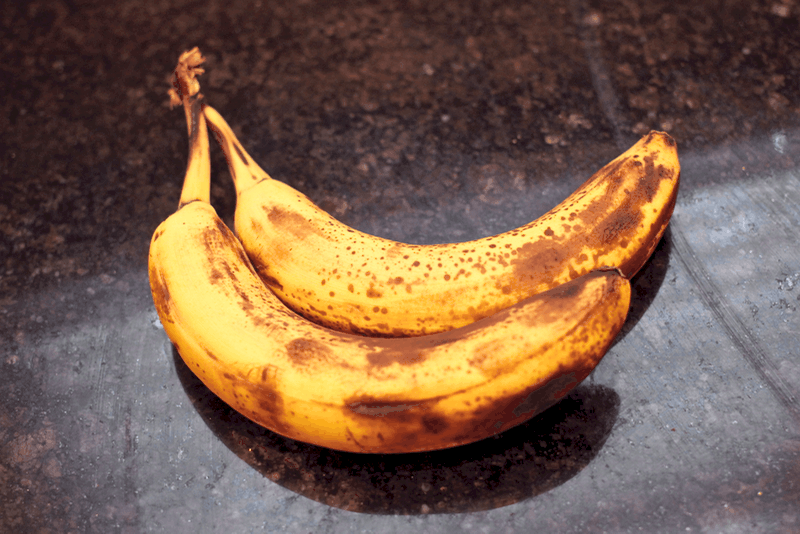 Two ripe bananas on a dark marble counter