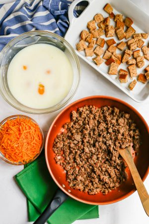 Ingredients laid out for making a breakfast casserole, including a pan of cooked, crumbled sausage, a bowl of shredded cheese, a bowl with eggs and milk and a casserole dish with cubed bread