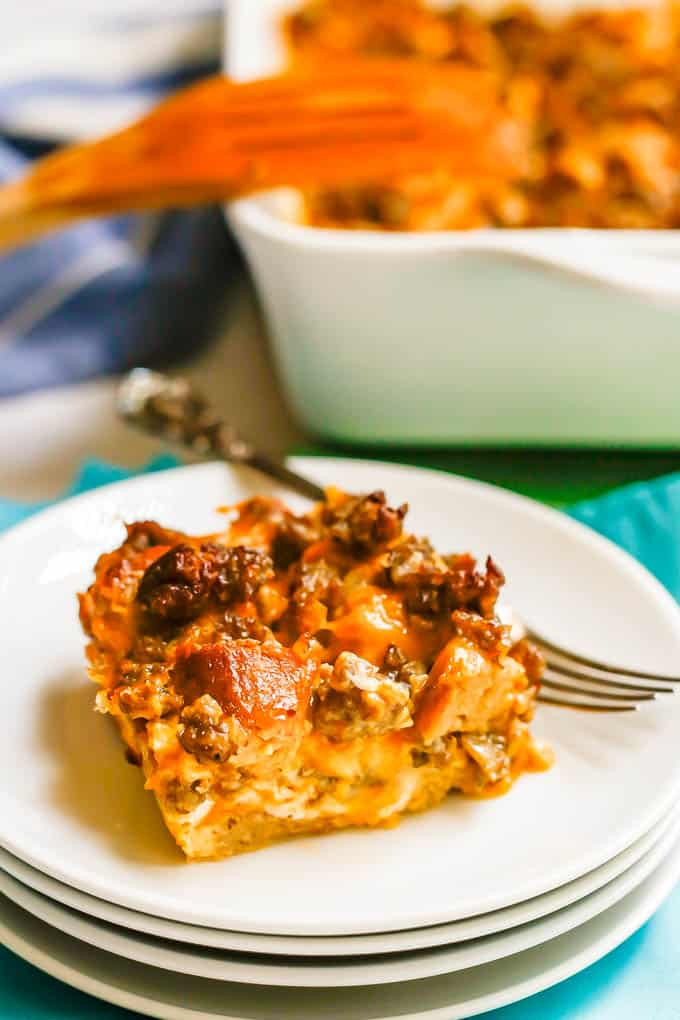 A serving of a sausage and egg breakfast casserole on a stack of white plates with a fork to the side