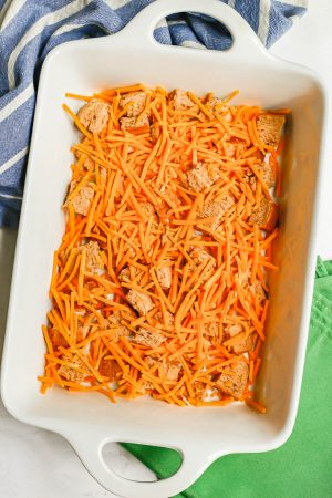 Cubed bread and shredded cheddar cheese in a large white baking dish