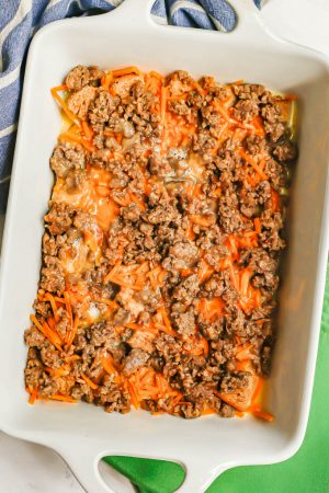 Cubed bread, shredded cheese, cooked, crumbled sausage and an egg mixture being layered in a white baking dish