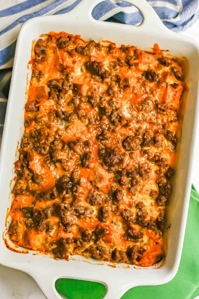 A baked breakfast casserole in a white baking dish with a blue striped towel behind and green napkins underneath