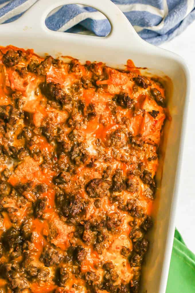 Close up of a cheesy baked breakfast casserole with crumbled sausage, bread and eggs