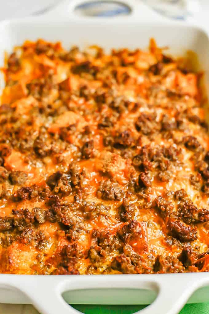 A cheesy sausage and egg breakfast casserole in a white baking dish