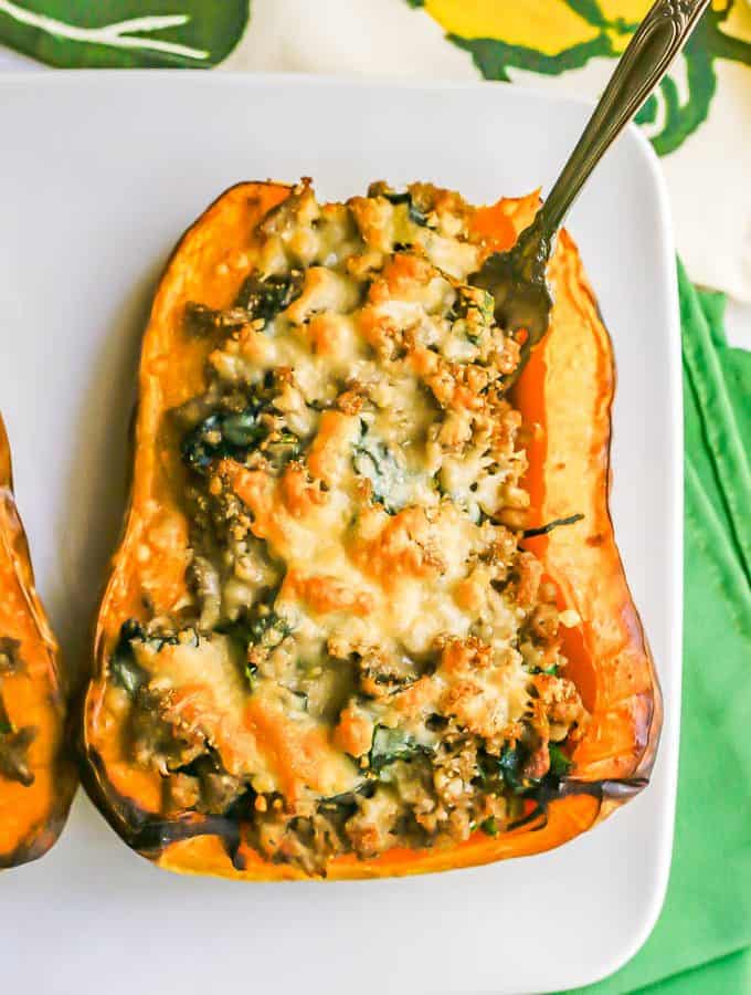Half of a butternut squash stuffed with turkey sausage and spinach and topped with browned Parmesan cheese with a fork stuck in it