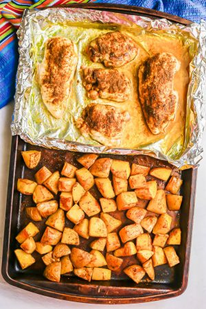 Roast chicken on a foil lined tray on a sheet pan with roasted potatoes on the other side