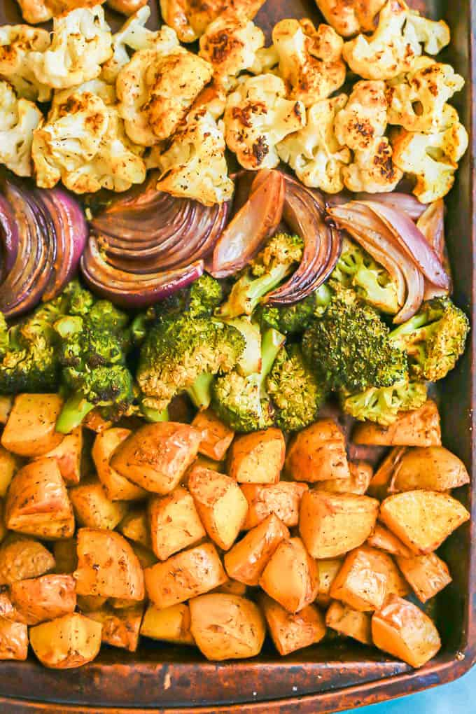 Close up of rows of arranged potatoes, broccoli, red onion and cauliflower on a sheet pan after roasting in the oven