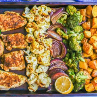 A sheet pan meal with spiced roasted chicken, cauliflower, red onion, broccoli and potatoes