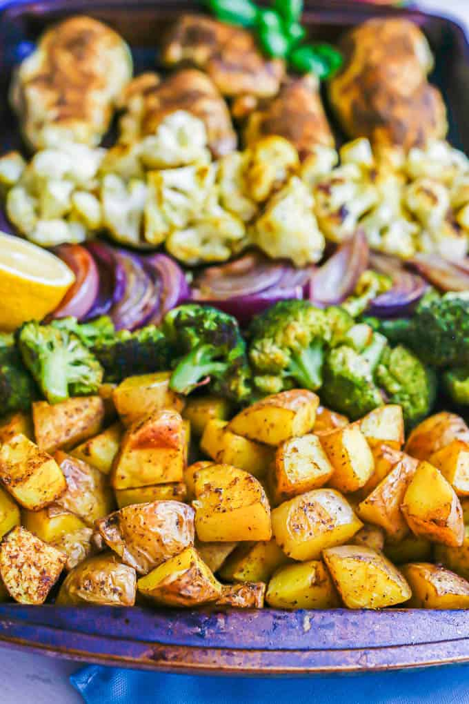 Close up of roasted potatoes on a sheet pan with chicken and other veggies