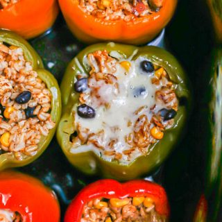 Six multi colored stuffed peppers in a slow cooker insert after being cooked with some melted cheese on one