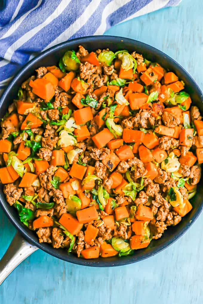 A large skillet with crumbled turkey sausage, cubed sweet potatoes and shredded Brussels sprouts