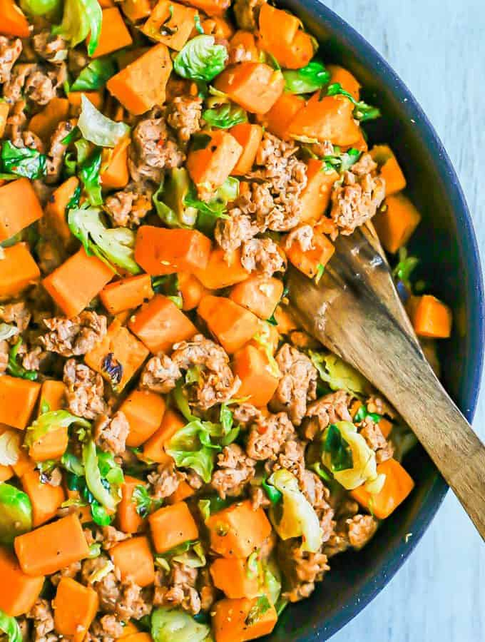 A large skillet with turkey sausage, sweet potatoes and Brussels sprouts with a wooden spoon resting in the pan